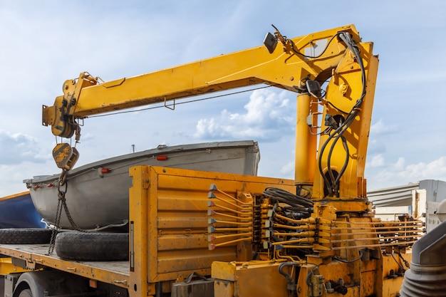Hydrauliczny dźwig samochodowy przygotowuje się do rozładowania łodzi wiosłowej z jego ciała