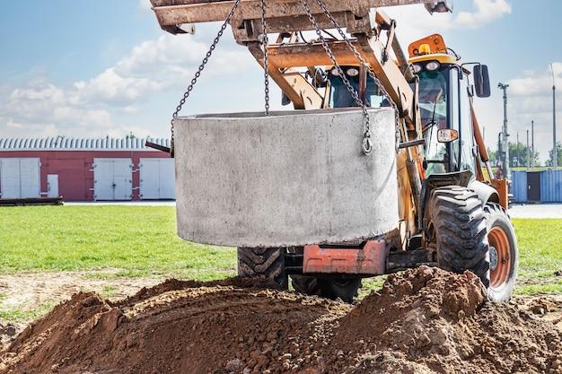 Hydrauliczny układ tłokowy koparki z łyżką, opuszczanie do wykopu na stalowych linkach betonowy pierścień kanalizacyjny. budowa lub naprawa domu kanalizacyjnego.
