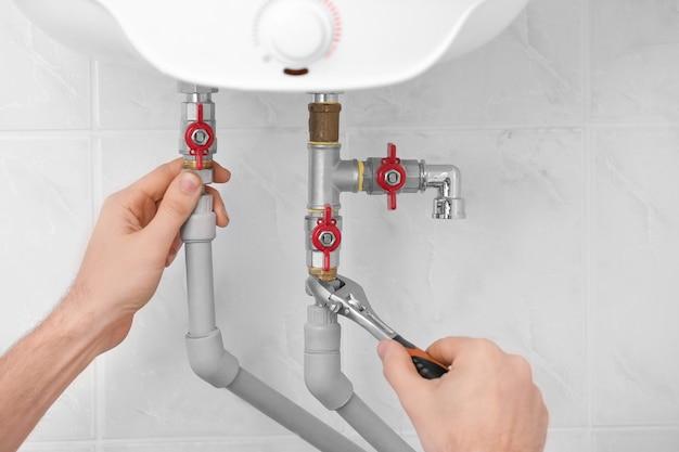 Hydraulik instalujący kocioł w łazience