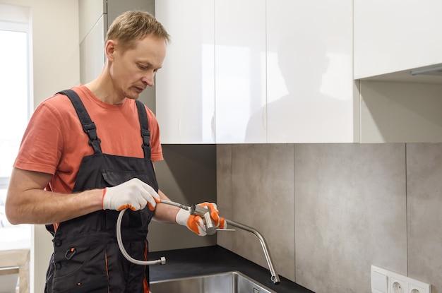 Hydraulik instalujący kran na zlewie kuchennym