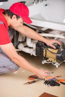 Hydraulik instaluje rury w domu, w łazience.
