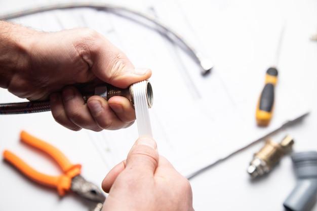 Hydraulik mężczyzna nakłada taśmę uszczelniającą na gwint złączki hydraulicznej