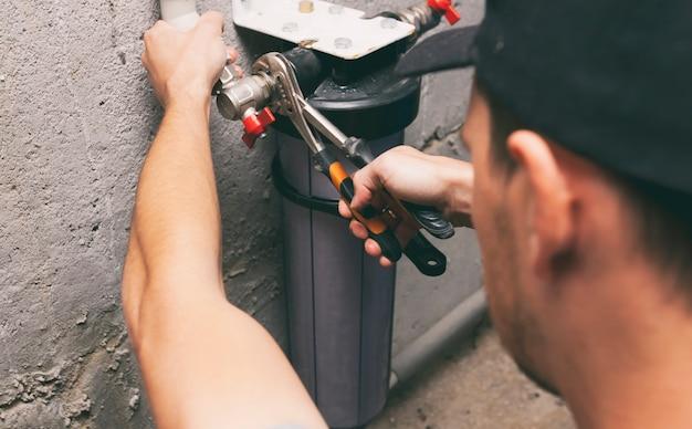 Hydraulik naprawiający filtr wody w piwnicy