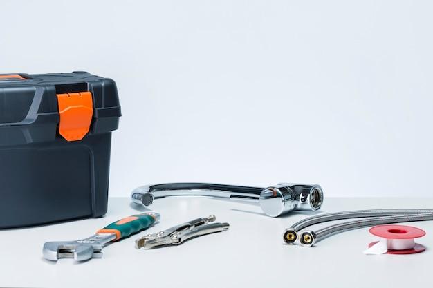 Hydraulik przy użyciu różnych narzędzi i osprzętu do naprawy kranu w łazience. skrzynki narzędziowe i kran z wodą na stole na szarym tle.