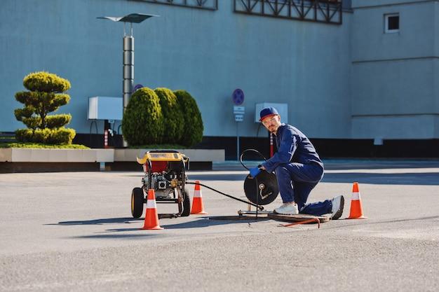 Hydraulik przygotowuje się do usunięcia problemu w kanalizacji. prace naprawcze przy rozwiązywaniu problemów.