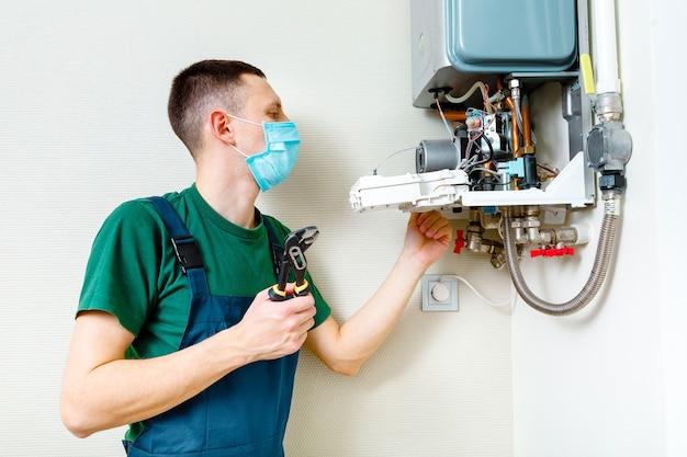 Hydraulik przyłącza się, próbując rozwiązać problem z mieszkalnym sprzętem grzewczym. naprawa kotła gazowego