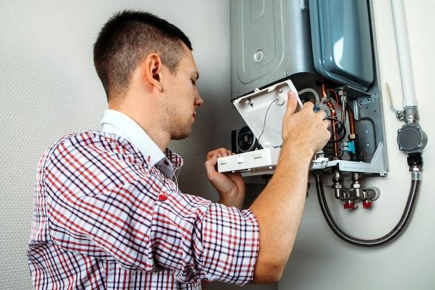 Hydraulik przyłącza się, próbując rozwiązać problem z mieszkalnym urządzeniem grzewczym. naprawa kotła gazowego
