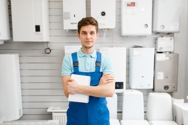 Hydraulik w mundurze na gablocie z kotłami w sklepie hydraulicznym. mężczyzna z notebookiem kupujący inżynierię sanitarną w sklepie, wybór kranów i kranów