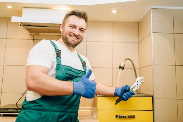 Hydraulik w mundurze pokazujący kciuki do góry, złota rączka. profesjonalny pracownik wykonuje naprawy wokół domu, usługi remontowe w domu