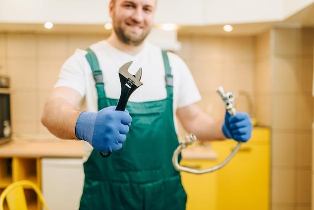 Hydraulik w mundurze trzyma klucz, złota rączka. profesjonalny pracownik wykonuje naprawy wokół domu, usługi remontowe w domu