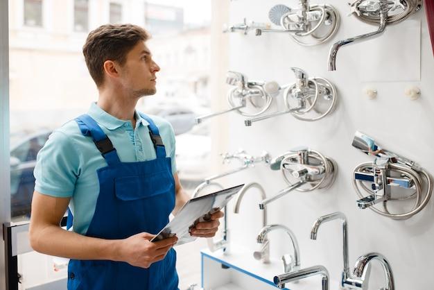 Hydraulik w mundurze w gablocie w sklepie hydraulicznym. mężczyzna z notebookiem kupujący inżynierię sanitarną w sklepie, wybór kranów i kranów