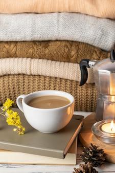Hygge lifestyle martwa kompozycja z kawą, świecami, książkami i dzianinowymi pledami lub swetrami