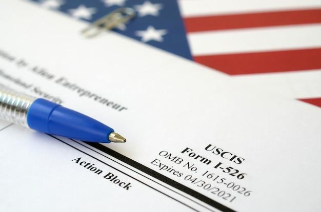 I-526 petycja dla imigrantów złożona przez alien entrepreneur pusty formularz leży na fladze stanów zjednoczonych z niebieskim długopisem z departamentu bezpieczeństwa wewnętrznego