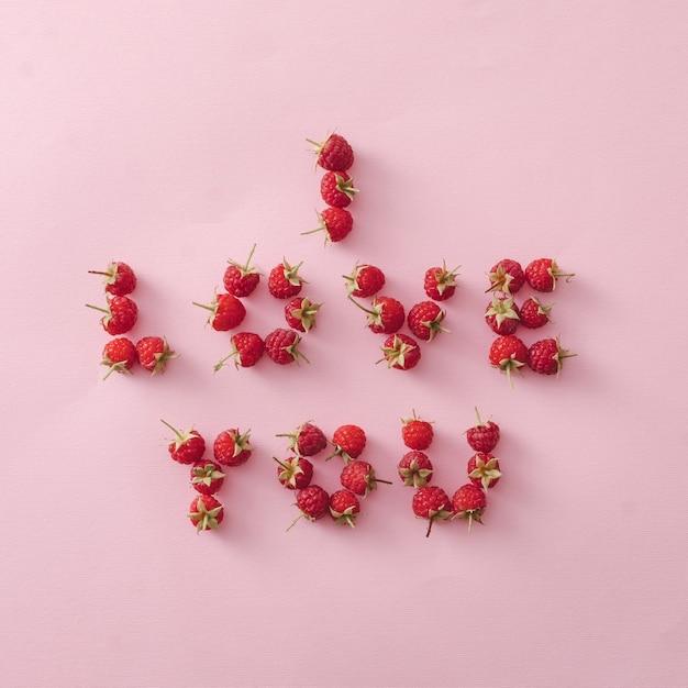 I love you romantyczny projekt kartki lub plakatu z dojrzałymi czerwonymi malinami tworzącymi wiadomość na różowym papierze dla ukochanej, walentynek, zaręczyn lub ślubu