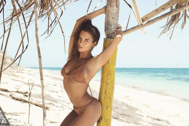 I piękna kobieta w beżowym bikini na dzikiej plaży