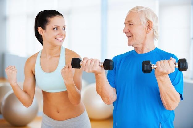 I trzy razy więcej. pewna siebie fizjoterapeutka pokazująca, jak wykonywać ćwiczenia siłowe starszemu mężczyźnie w klubie fitness