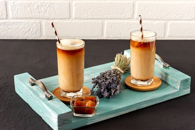 Iced levender kawa napój w szklance z bąbelkową pianką na drewnianej tacy.