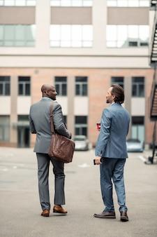 Idąc do biura. ciemnoskóry biznesmen ze skórzaną torbą idący do biura z kolegą