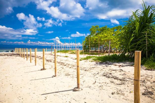 Idealna biała plaża z turkusową wodą i małym płotem na bezludnej wyspie