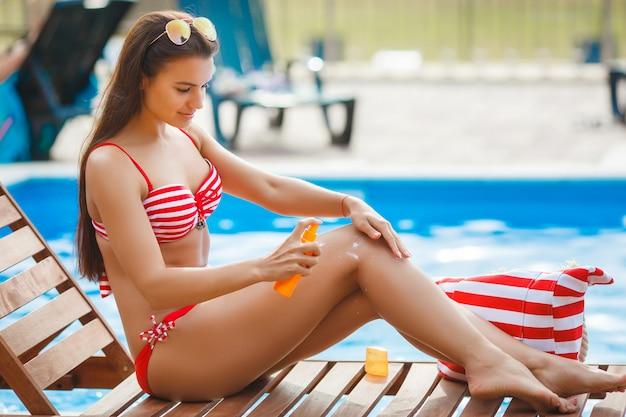 Idealna kobieta w pobliżu opalania w basenie. młoda piękna dziewczyna ma opalanie. ładna kobieta relaksuje przy plażą