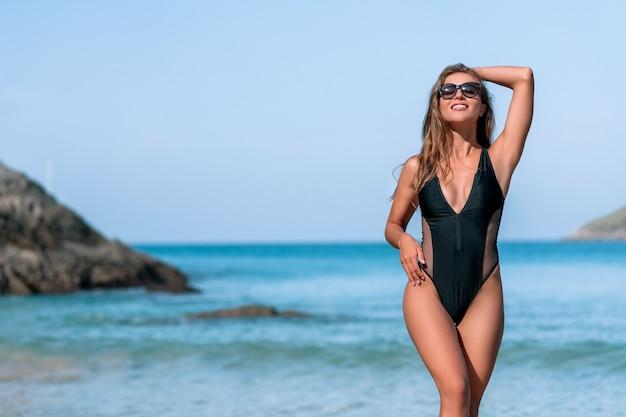 Idealna kobieta w stylowych czarnych strojach kąpielowych pozuje na rajskiej tropikalnej plaży