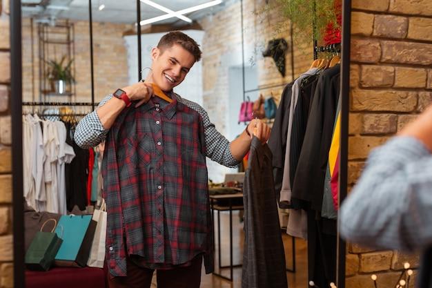 Idealna koszula. wesoły, emocjonalny młody człowiek czuje się zadowolony z nowych pięknych ubrań podczas wizyty w nowoczesnym sklepie z ubraniami i patrząc na swoje odbicie w lustrze