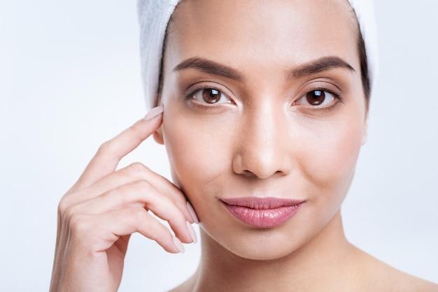 Idealna metoda suszenia włosów. zbliżenie na piękną ciemnowłosą kobietę suszącą włosy metodą turban z ręcznikiem i uśmiechniętą