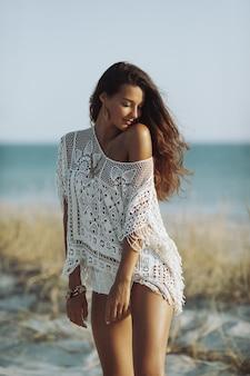 Idealna młoda kobieta boho stojąca na piaszczystej plaży tropikalnej przed pięknym bokeh kopii przestrzeni