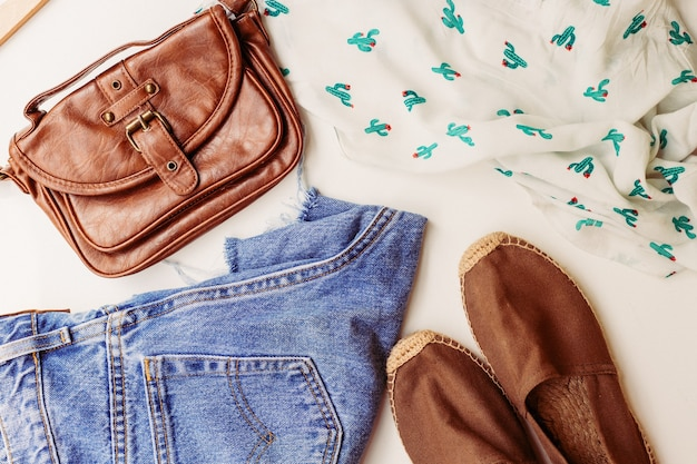 Idealna odzież na letnie stylizacje: koszula, jeansy, torba, buty. widok z góry.