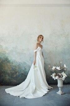 Idealna panna młoda, portret dziewczyny w długiej białej sukni. piękne włosy i czysta delikatna skóra. blond kobieta fryzurę ślubną