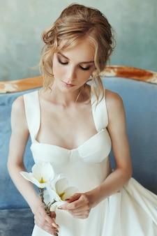 Idealna panna młoda, portret dziewczyny w długiej białej sukni. piękne włosy i czysta delikatna skóra. ślubna fryzura blond kobieta. dziewczyna z białym kwiatem w dłoniach