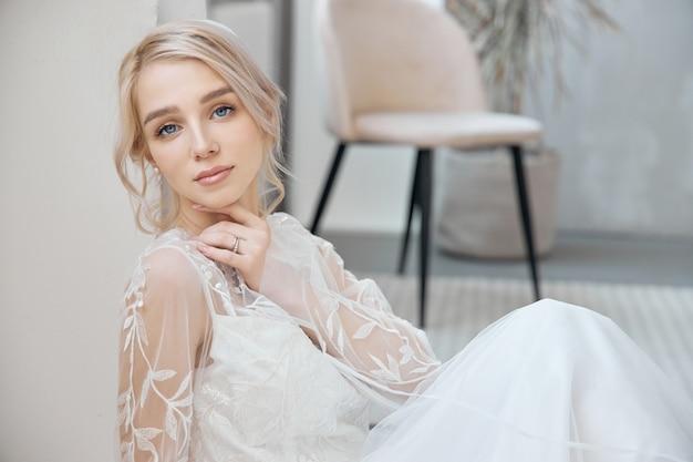 Idealna panna młoda siedząca na podłodze, portret dziewczyny w długiej białej sukni. piękne włosy i czysta, miękka skóra