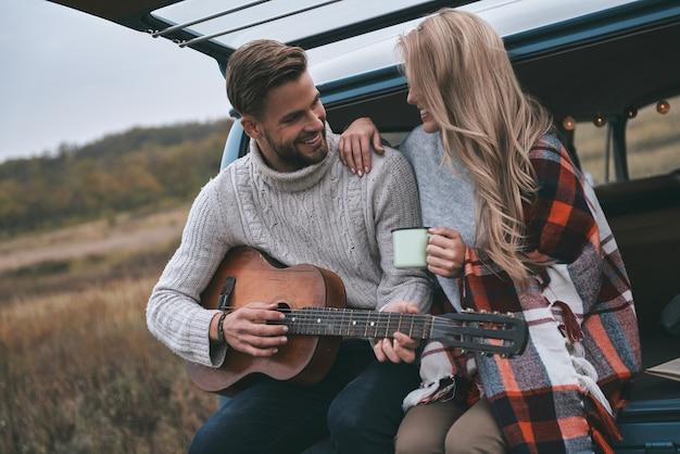Idealna randka. przystojny młody mężczyzna gra na gitarze dla swojej pięknej dziewczyny, siedząc w bagażniku niebieskiego mini vana w stylu retro
