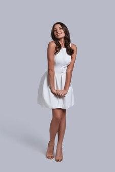 Idealna suczka. pełna długość atrakcyjnej młodej kobiety w białej sukni, patrzącej w kamerę i uśmiechającej się, pozując na szarym tle