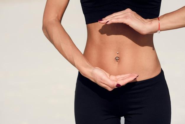 Idealna talia. pojęcie zdrowego odżywiania. szczupły brzuch sportowy młodej kobiety, używając rąk, pokazuje równowagę.