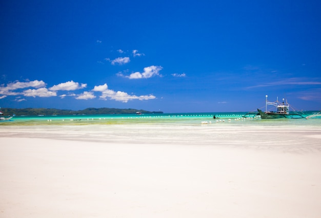 Idealna tropikalna piaszczysta plaża z turkusową wodą i małymi żaglówkami