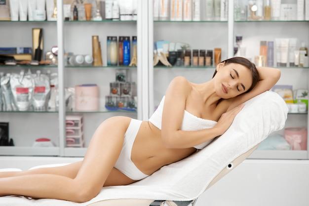 Idealne ciało i doskonała skóra ładnej kobiety po zabiegach spa w gabinecie kosmetycznym