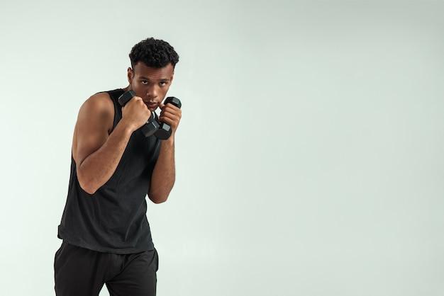Idealne ciało. muskularny młody człowiek afryki ćwiczenia z hantlami stojąc na szarym tle. strzał studio. koncepcja sportowa