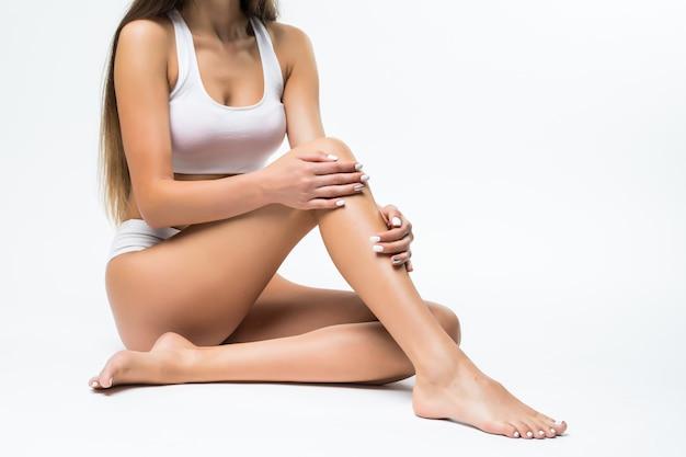 Idealne ciało, piękna kobieta. model dziewczyna z pięknym ciałem - nogi, ramiona, ramiona, siedząc na podłodze. zdrowie i uroda kobieta w białej bieliźnie dotykając jej skóry.