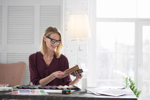 Idealne dopasowanie. atrakcyjna projektantka wybierając tapicerkę i uśmiechnięta