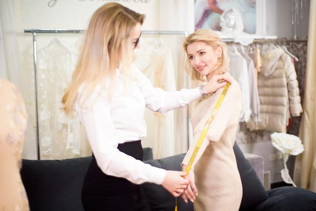 Idealne dopasowanie. projektantka mody i klientka mierząca długość rękawa na odzież szytą na miarę w atelier.