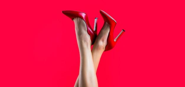 Idealne kobiece nogi na wysokich obcasach. zgrabne nogi, dziewczyna w butach na wysokim obcasie. buty na wysokim obcasie. piękne nogi kobiety. ładne kobiece nogi z czerwonymi szpilkami na czerwonym tle.