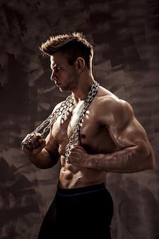 Idealne męskie ciało - niesamowite pozowanie kulturysta. trzymaj łańcuch z tatuażem
