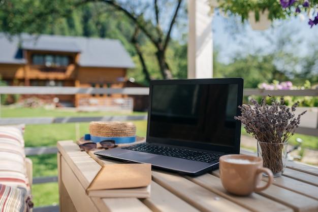 Idealne miejsce do pracy latem. laptop, notatnik i filiżanka kawy są na drewnianym stole. koncepcja biznesowa zdjęcie