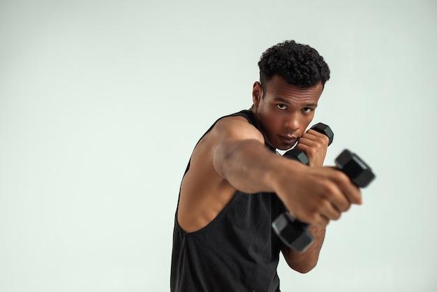 Idealne mięśnie. muskularny młody człowiek afryki ćwiczenia z hantlami stojąc na szarym tle. strzał studio. koncepcja sportowa