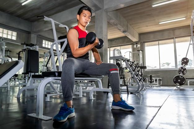 Idealne silny kulturysta wysportowany azjatycki człowiek ramię treningu z hantle na siłowni.