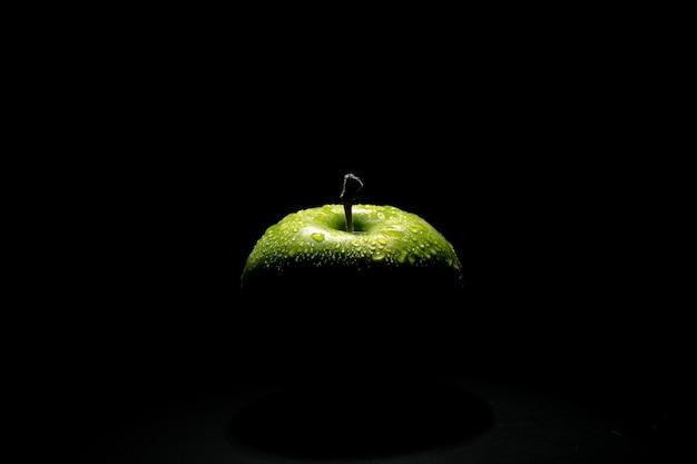 Idealne świeże zielone jabłko z kroplą wody na czarno