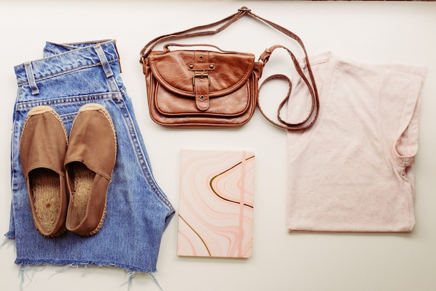 Idealne ubrania na letnie stylizacje: koszula, dżinsy, torba, buty. widok z góry.