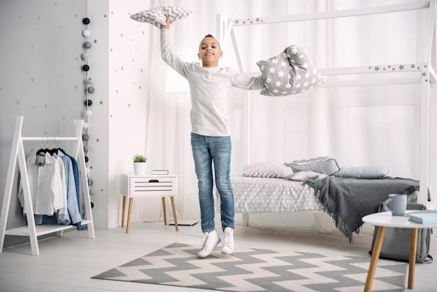 Idealne weekendy. energiczny chłopiec afroamerykanin skaczący trzymając poduszki