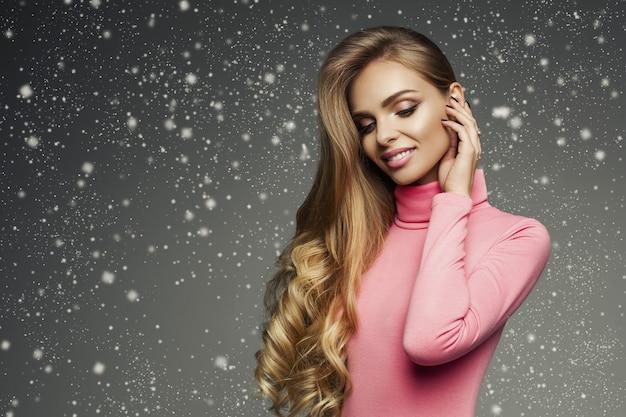 Idealnie uśmiechnięta blondynka w różowym swetrze pod opadami śniegu